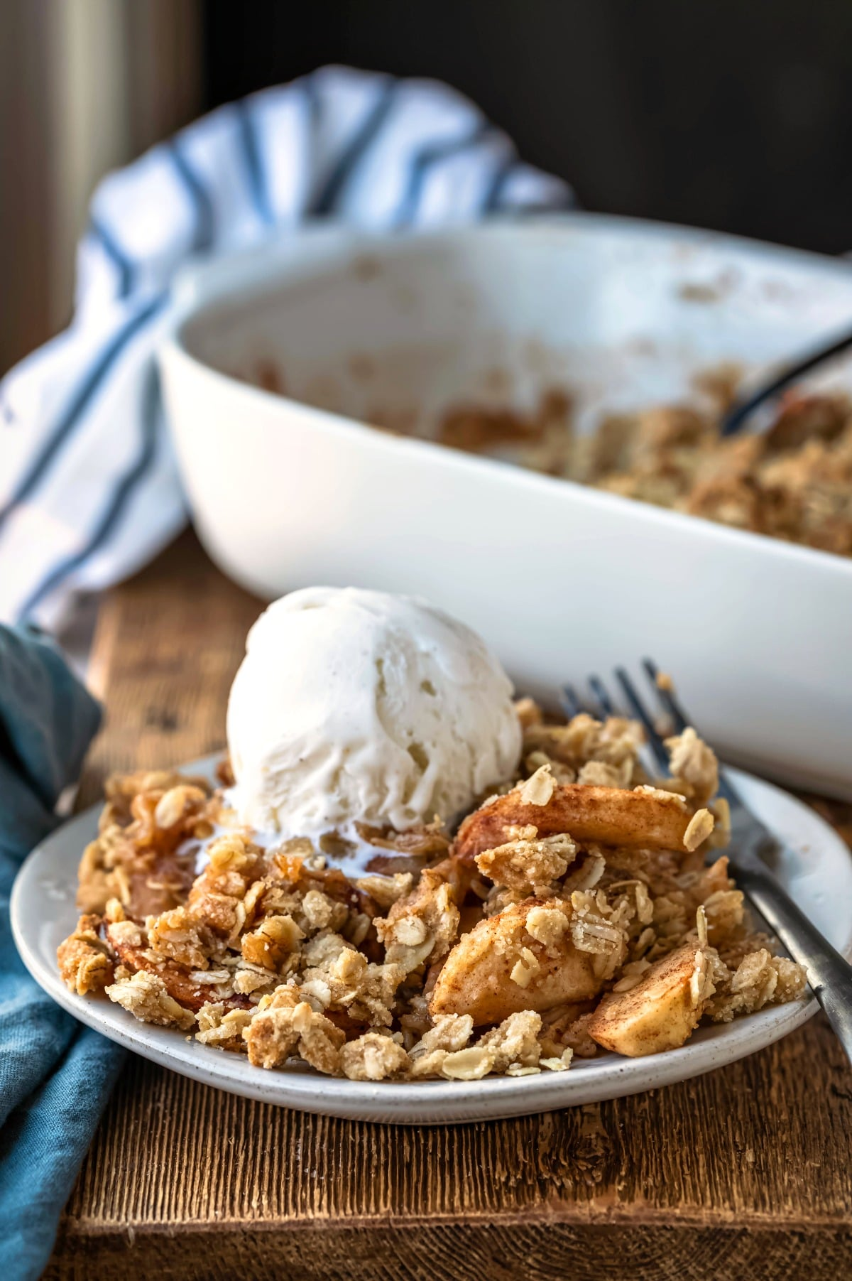 Apple crisp topped with a scoop of vanilla ice cream