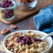 Instant pot steel cut oats in a white dish topped with dried cranberries