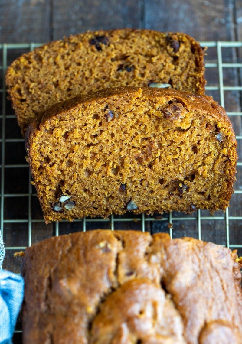 Two slices of pumpkin nut bread on a wire cooling rack