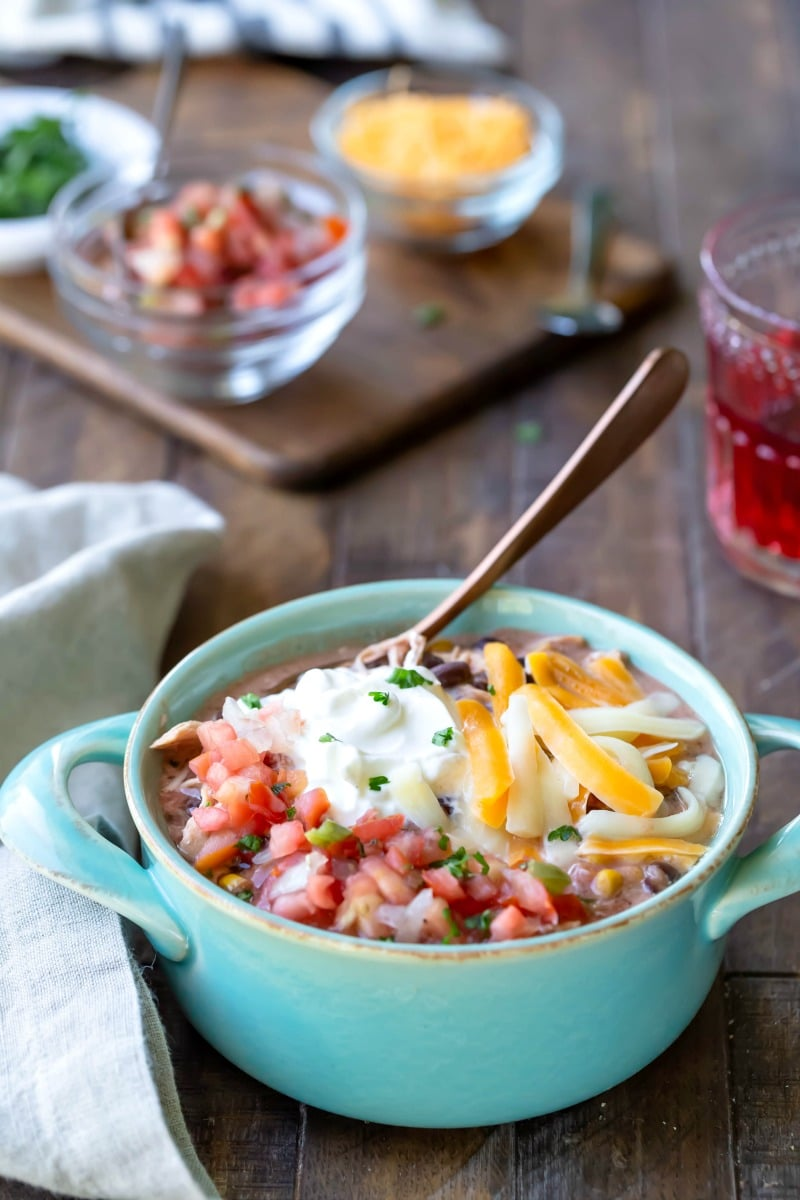 Bowl of slow cooker chicken enchilada chili next to dishes of pico de gallo, cheese, and cilantro
