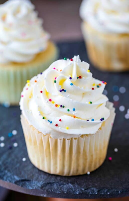 Vanilla cupcake topped with vanilla buttercream and sprinkle balls