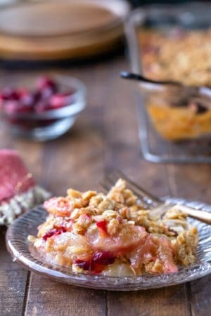 Cranberry apple crisp on a glass plate with a gold fork