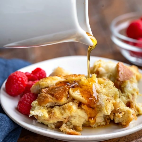 White carafe pouring maple syrup onto crock pot French toast