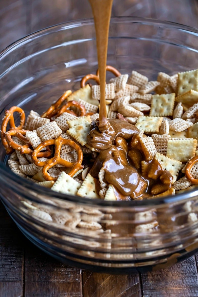 Toffee pouring onto bowl with Chex mix