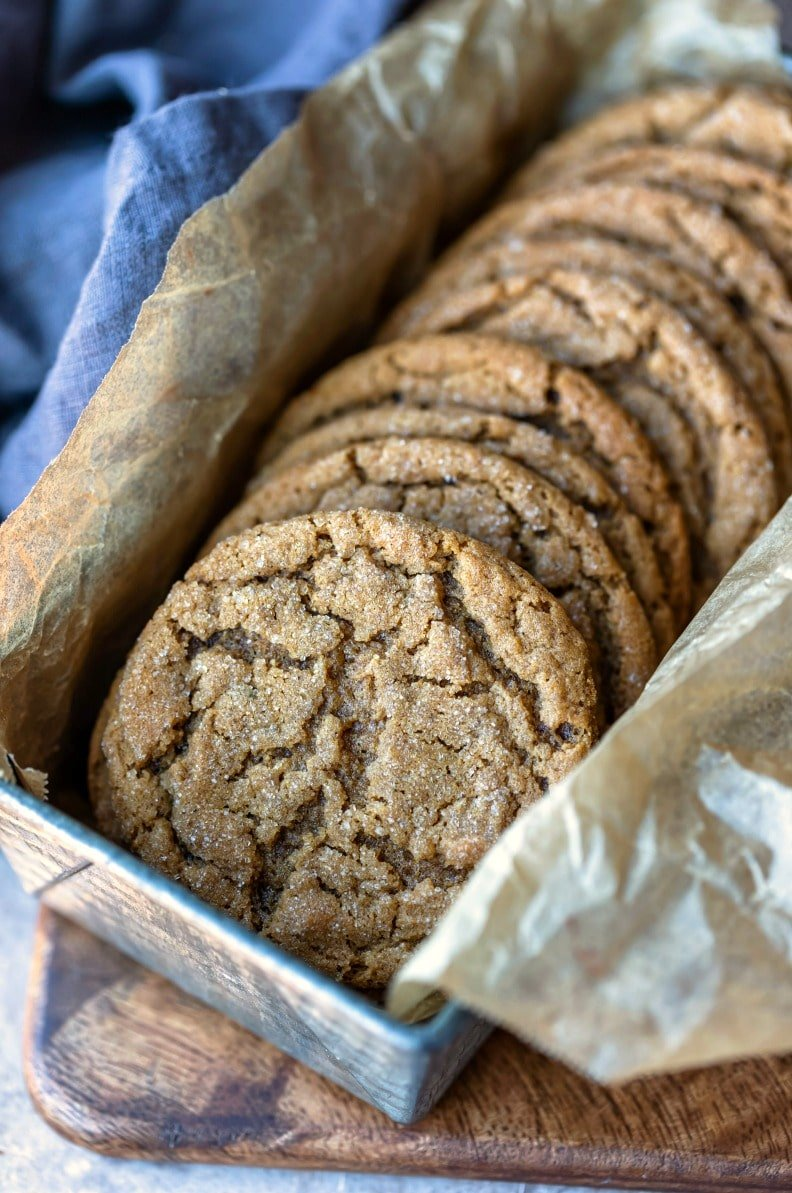 Stack of molasses cookies in a silver tin