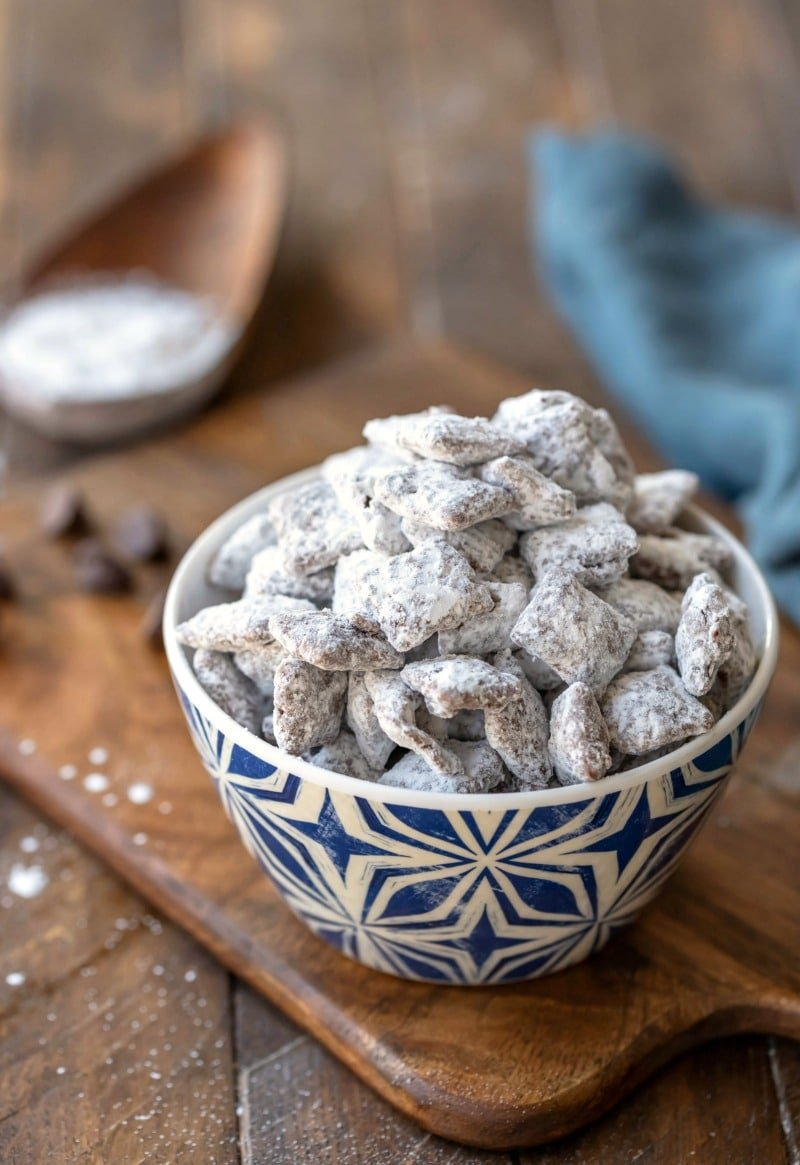 Bowl of puppy chow muddy buddies on a wooden cutting board