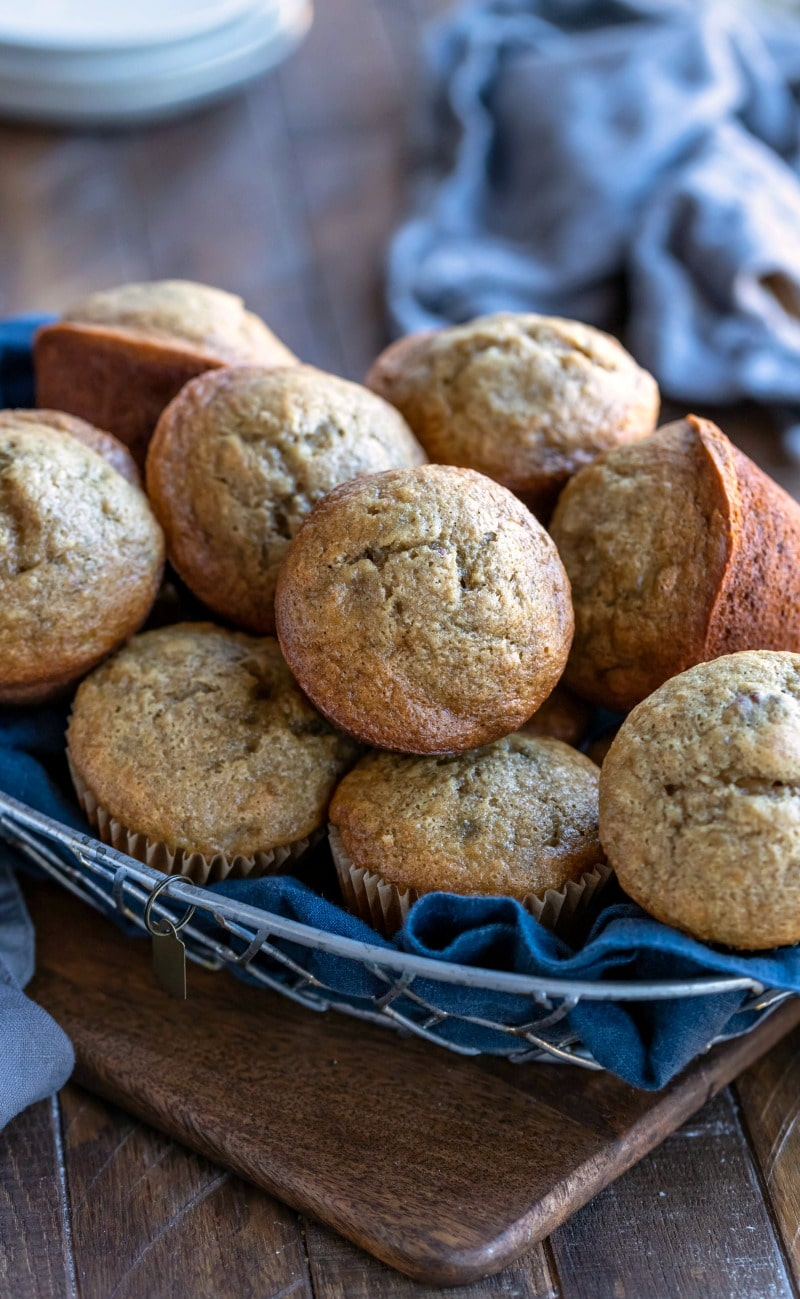Basket of banana bread muffins on a wood cutting board