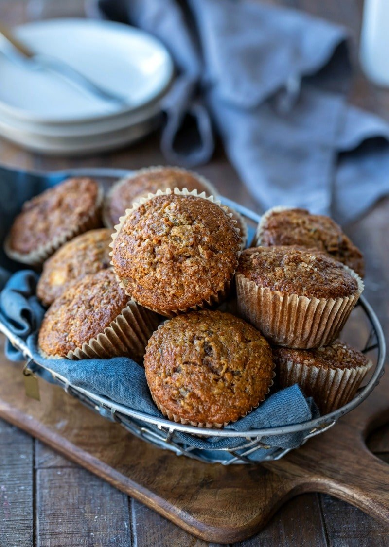 Basket of morning glory muffins on a wooden cutting board
