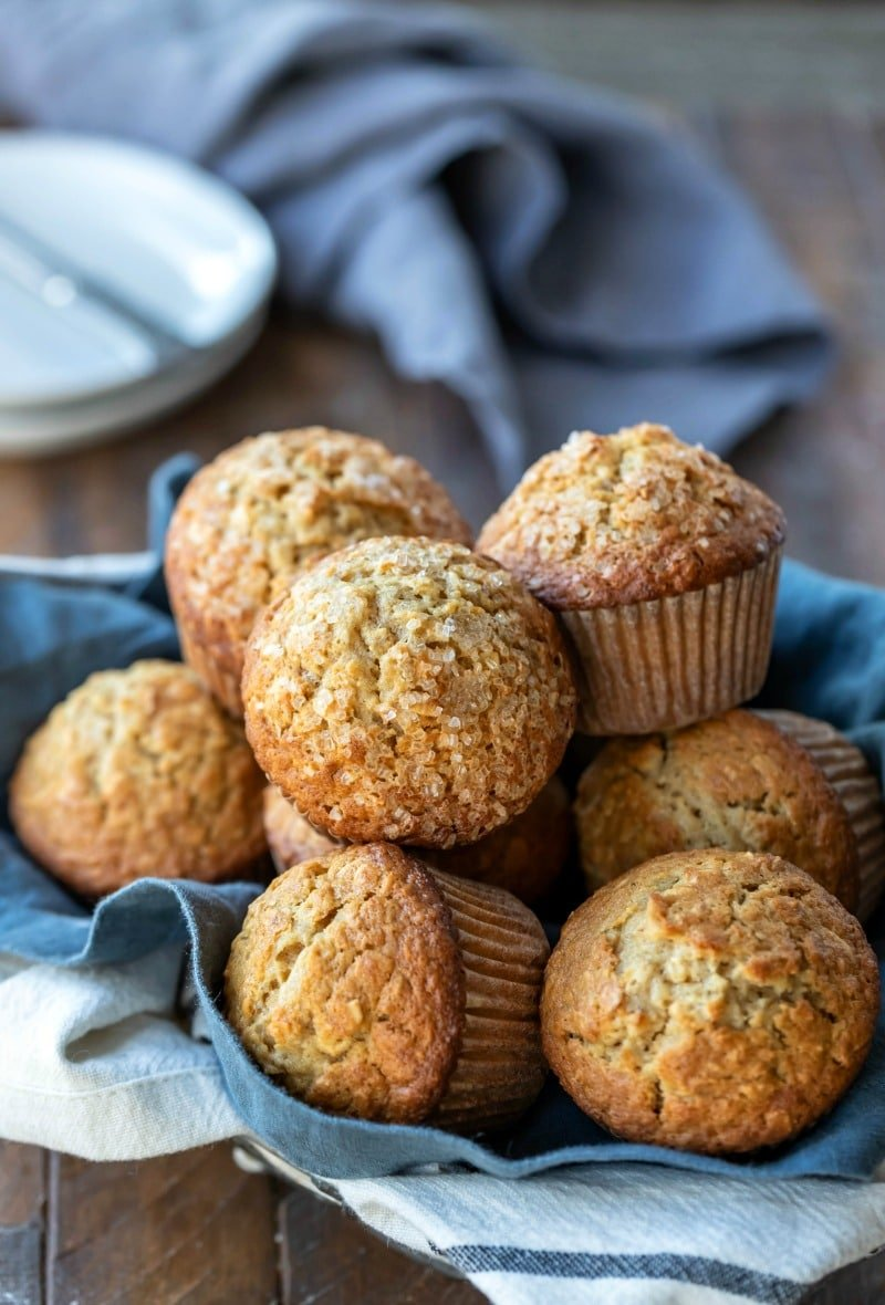 Maple brown sugar oatmeal muffins next to a stack of white plates