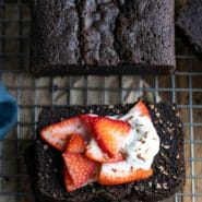 Slices of chocolate pound cake topped with strawberries and whipped cream