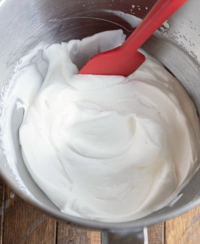 Whipped cream in a silver mixing bowl
