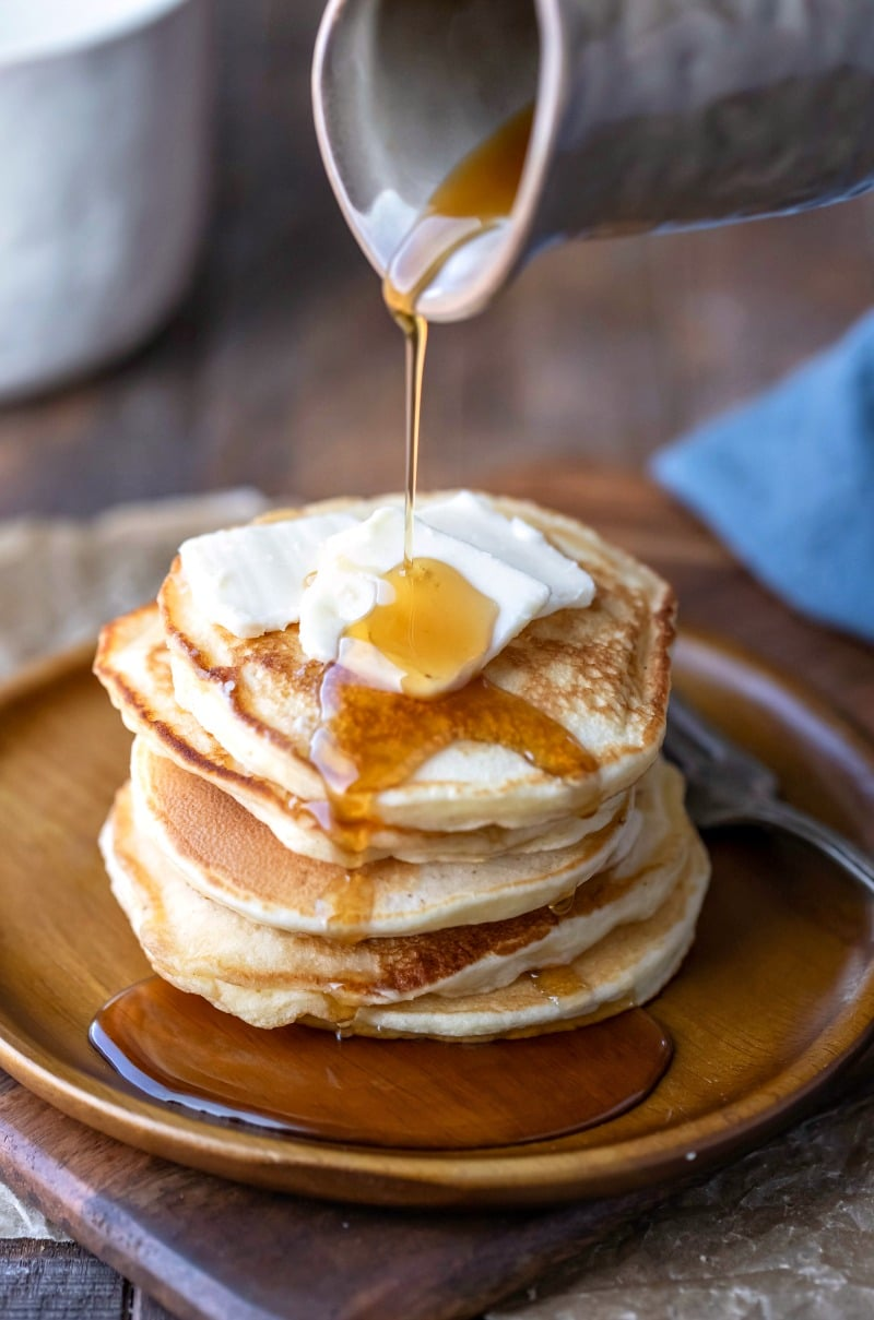 Maple syrup pouring onto sour cream pancakes