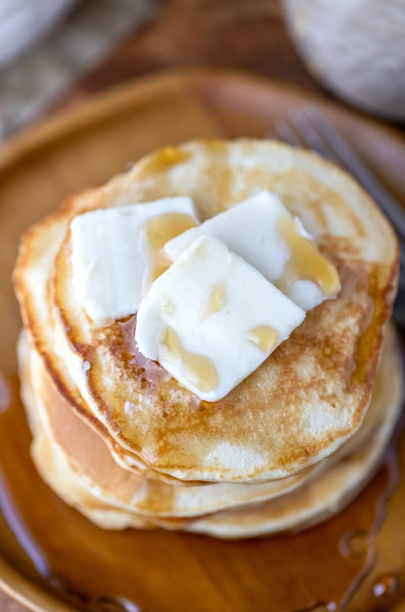 Close up photo of sour cream pancakes topped with butter pats