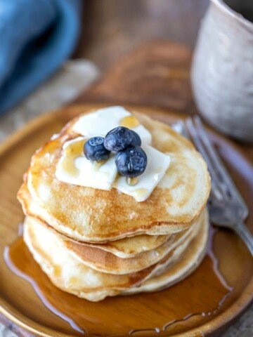 Stack of sour cream pancakes topped with butter syrup and blueberries