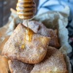 Honey dipper drizzling honey onto a sopaipilla