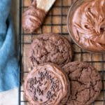 Three chocolate frosted cookies on a wire cooling rack