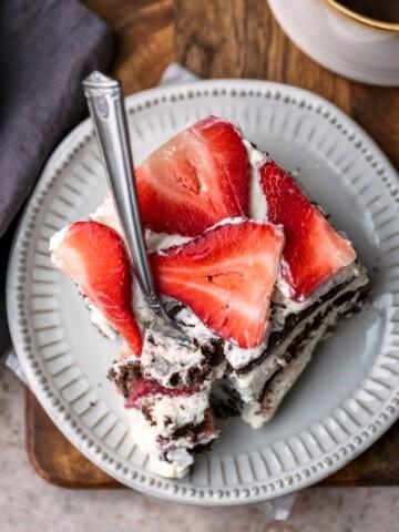 Slice of strawberry icebox cake on a cream plate