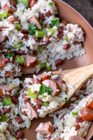 Red beans and rice in a skillet wiht a wooden spoon in it
