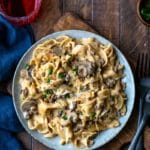 Blue plate with Instant Pot Beef Stroganoff next to two black forks