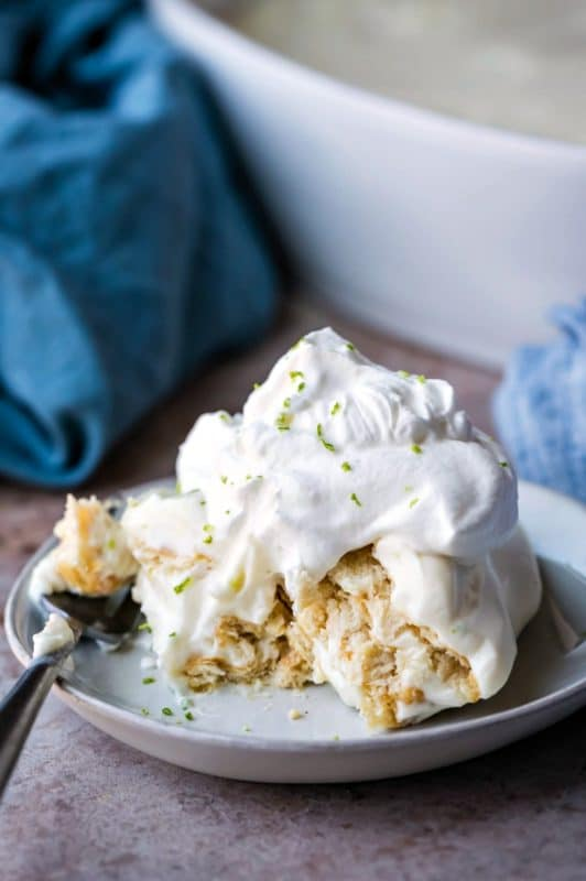 Piece of no bake key lime pie topped with whipped cream and lime zest