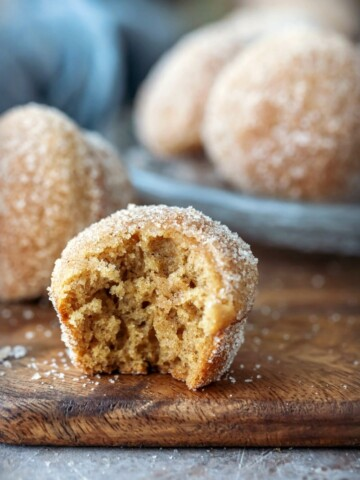 Apple cider donut muffins on a wooden cutting board