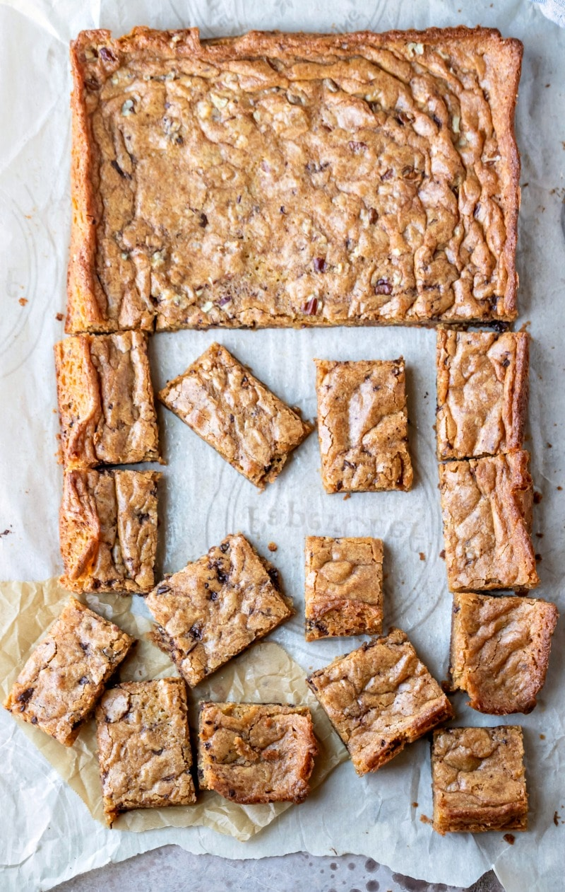Cut tray of blondies on white parchment paper