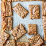 Partially cut tray of blondies on parchment paper