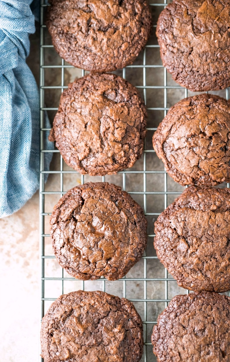 Chocolate fudge cookies on a wire cooling rack next to a blue linen napkin