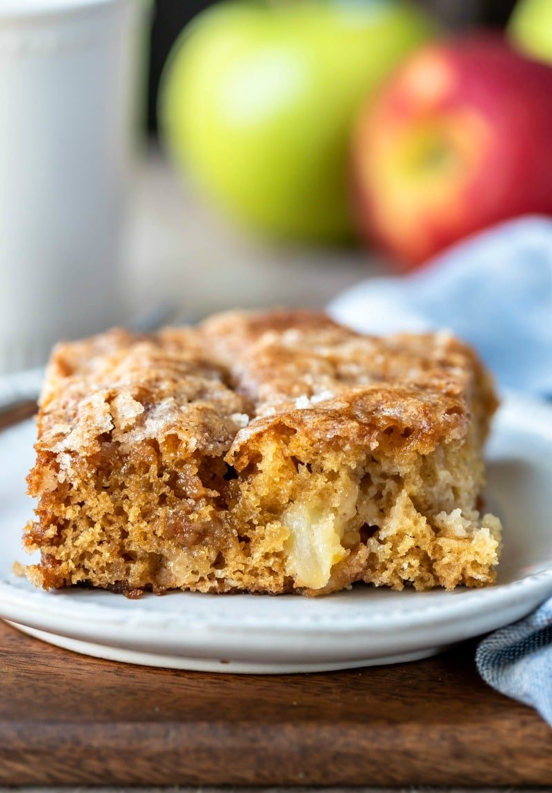 Slice of cinnamon apple cake next to red and green apples