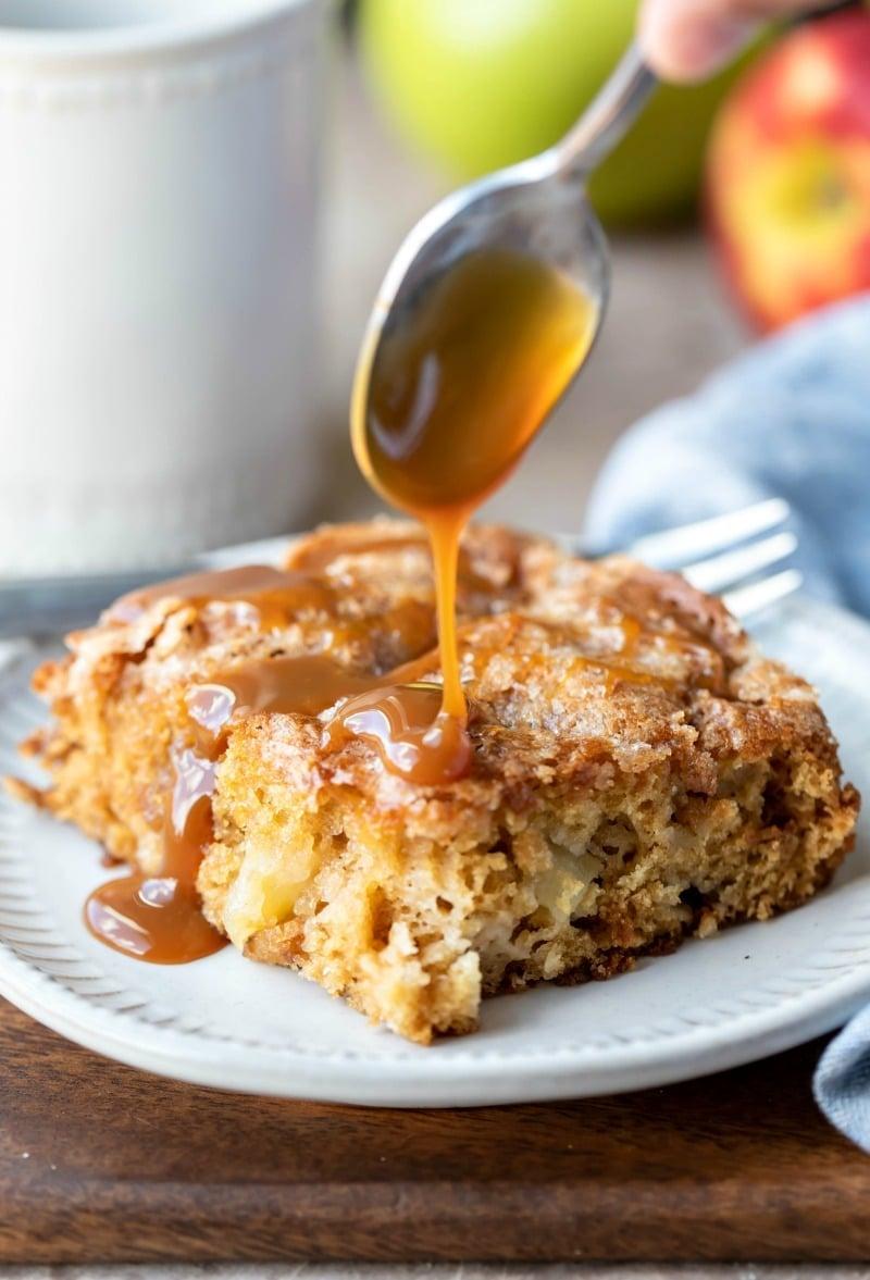 Spoon drizzling caramel on top of cinnamon apple cake