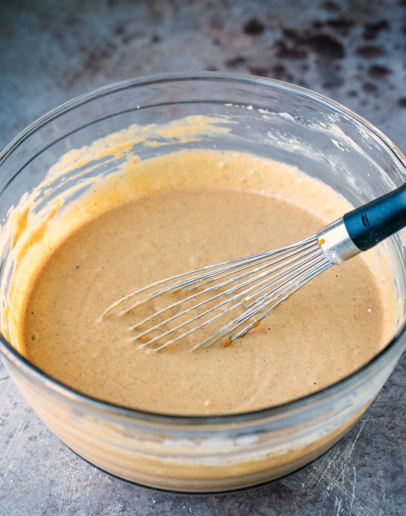 Pumpkin pancake batter with a whisk in it