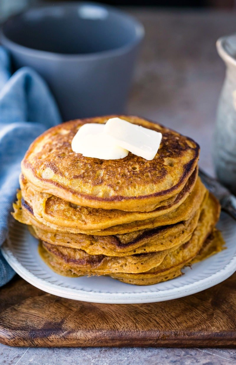 Stack of pumpkin pancakes with three pats of butter on top