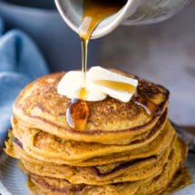 Crock of maple syrup pouring onto stack of pumpkin pancakes