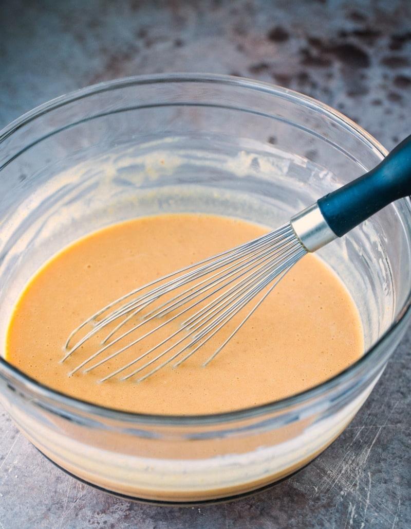 Pumpkin pancake batter in a glass mixing bowl