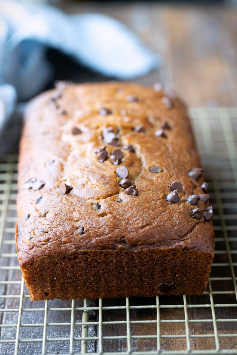 Loaf of pumpkin chocolate chip bread on a cooling rack