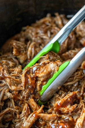 Green tongs picking up crockpot pulled pork