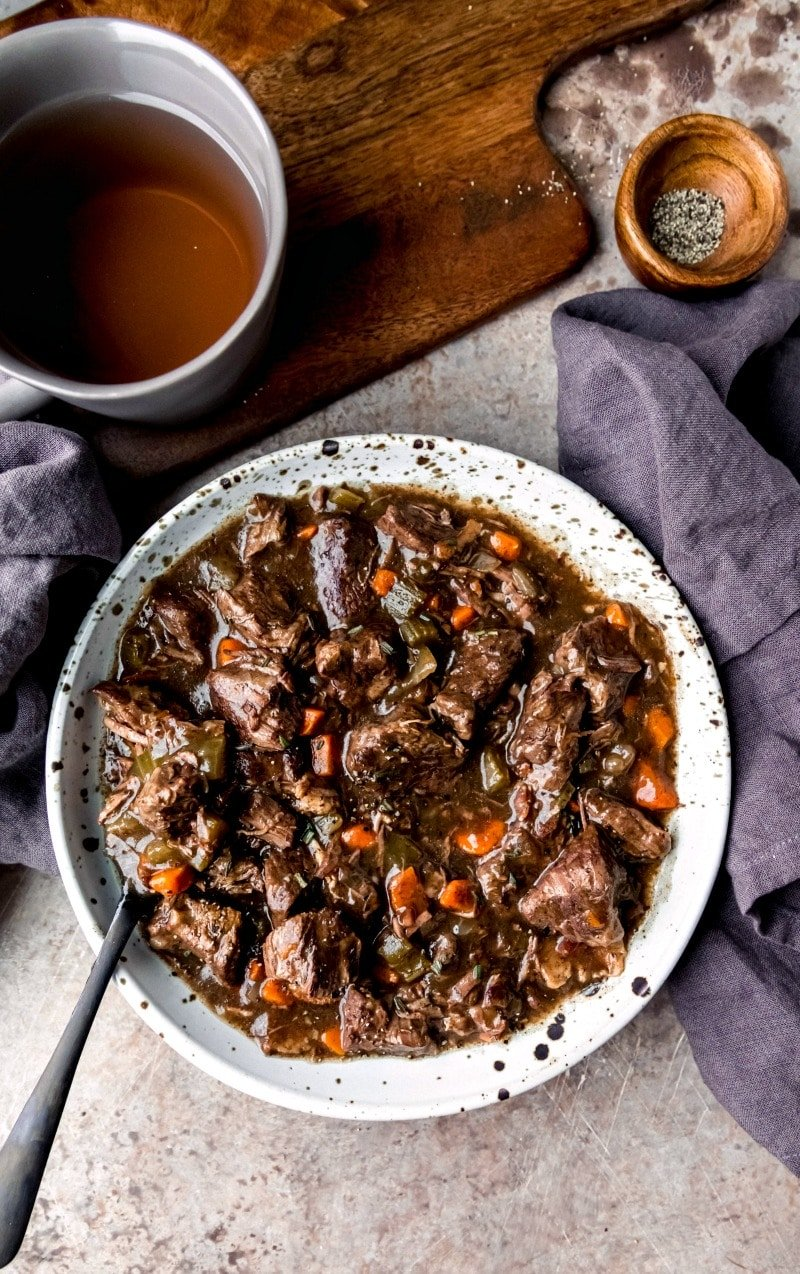 Dish of slow cooker beef bourguignon with a black spoon in it