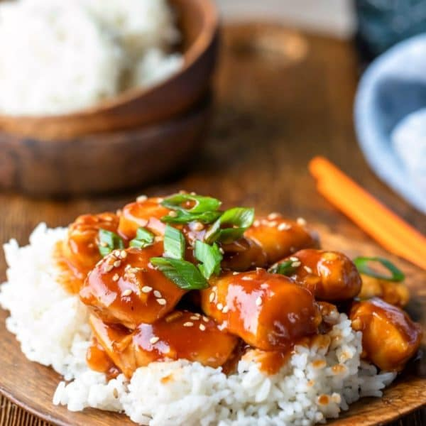 Easy orange chicken topped with sesame seeds and green onions