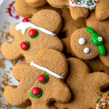 Christmas plate stacked with cut out gingerbread men cookies