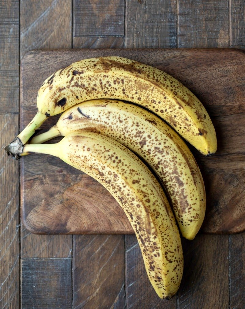 Speckled bananas on a wooden cutting board