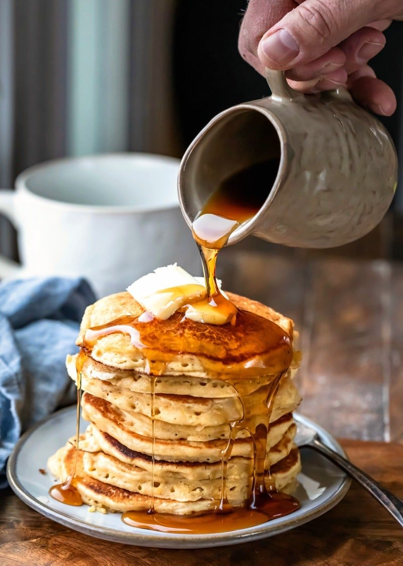 Stack of multigrain pancakes with butter and syrup on top