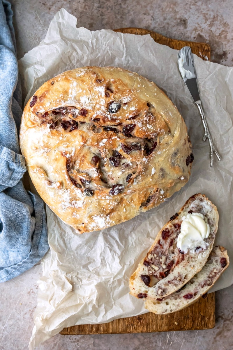 No Knead Cranberry Nut Bread with two slices cut and partially buttered