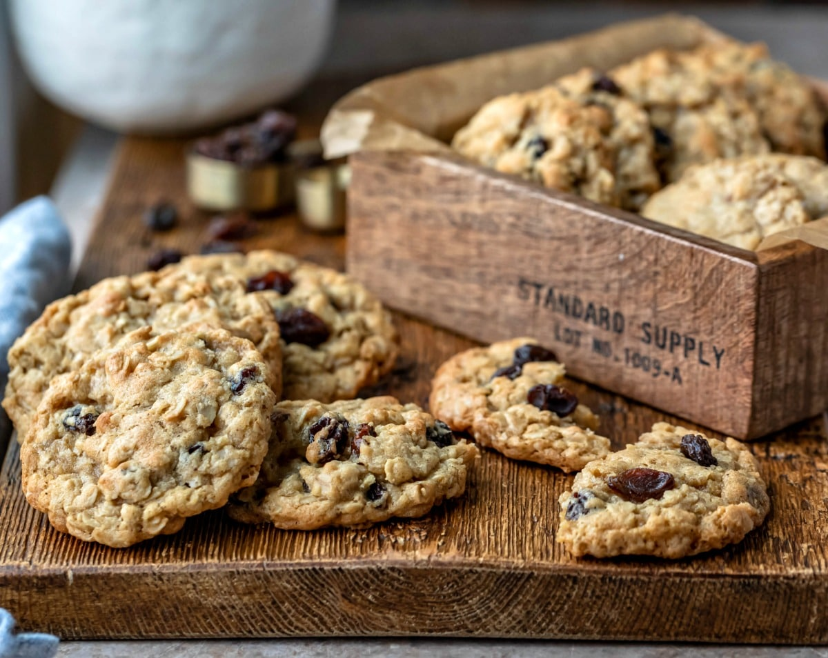 Stack of oatmeal raisin cookies next to a measuring spoon with raisins in it