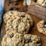Stack of oatmeal raisin cookies with dark raisins around them