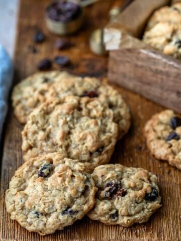 Stack of oatmeal raisin cookies with dark raisins around them
