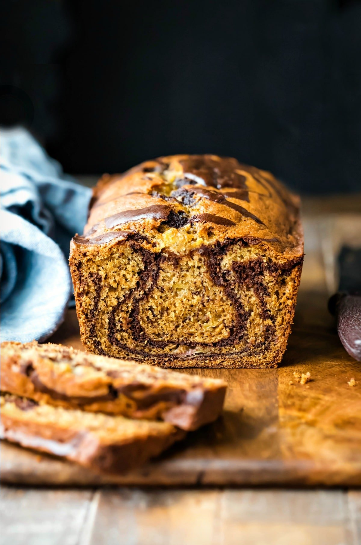 Loaf of marbled banana bread next to a blue linen napkin