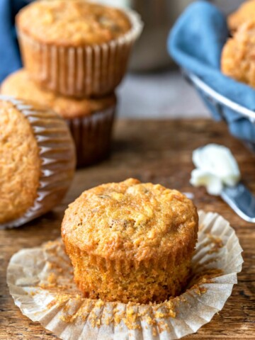 Unwrapped carrot cake muffin next to a butter knife with butter
