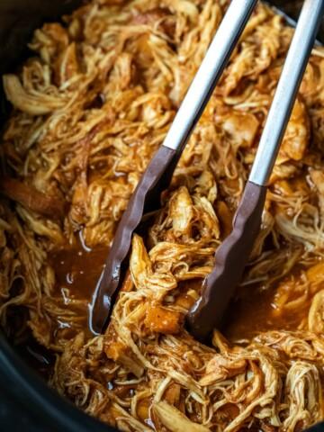 Tongs grabbing crock pot brown sugar bourbon bbq chicken in a crock pot