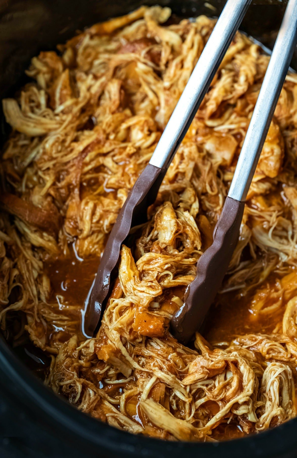 Tongs grabbing crock pot brown sugar bourbon bbq chicken in a crock pot