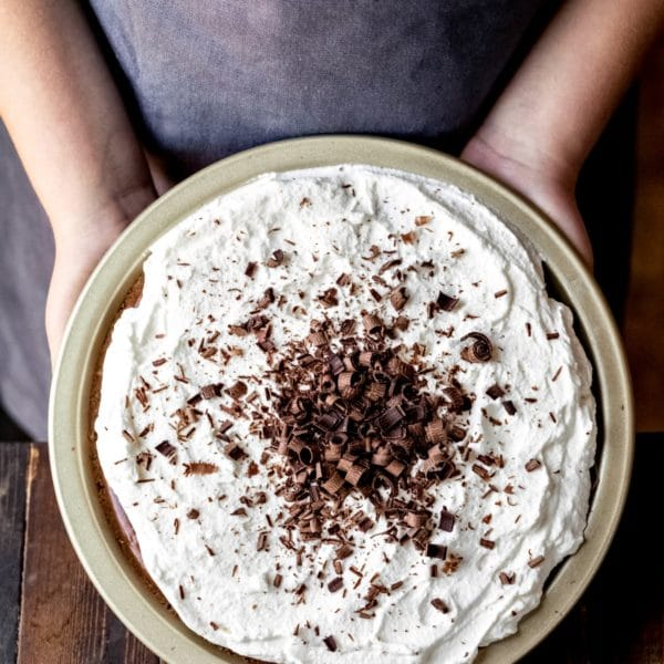 Two hands holding a no bake chocolate pie in a pan